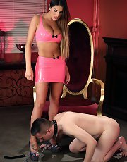 Mistress August Ames looks hot in her pink latex - with a chastised slave on her leash.